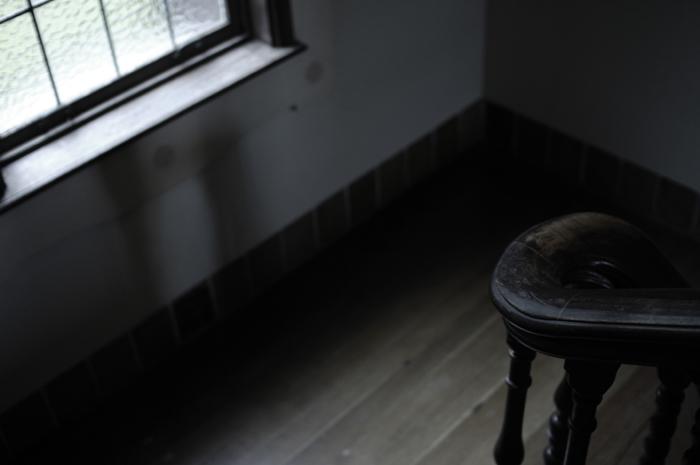 階段の踊り場に木の手すりと細長い窓にはステンドグラス越しに光が差していました。