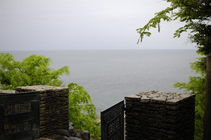 腰高までの石積みが左右にあり低い鉄の門を入れて海を覗いてみました。あいにくの雨で海はグレーですが、すぐ横には小さな芝生の庭もあり、一人でなければコーヒーでも飲みたい所でした。
