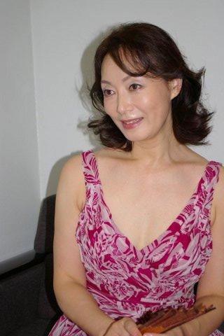 赤いワンピース姿で扇子を手に持って座る島田陽子