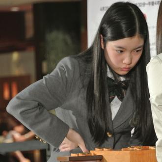 腰に手を当てて考慮している竹俣紅研修会員 日本将棋連盟ツイッター支部