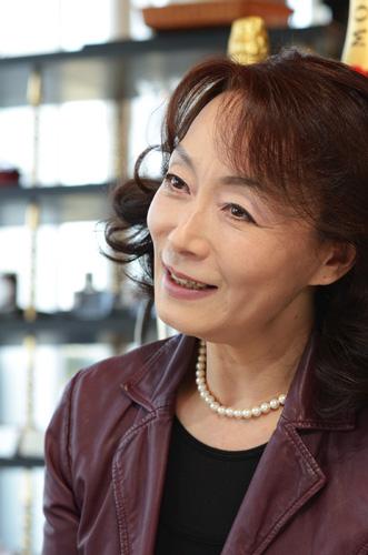 赤いジャケットを着て元気な笑顔を見せる島田陽子