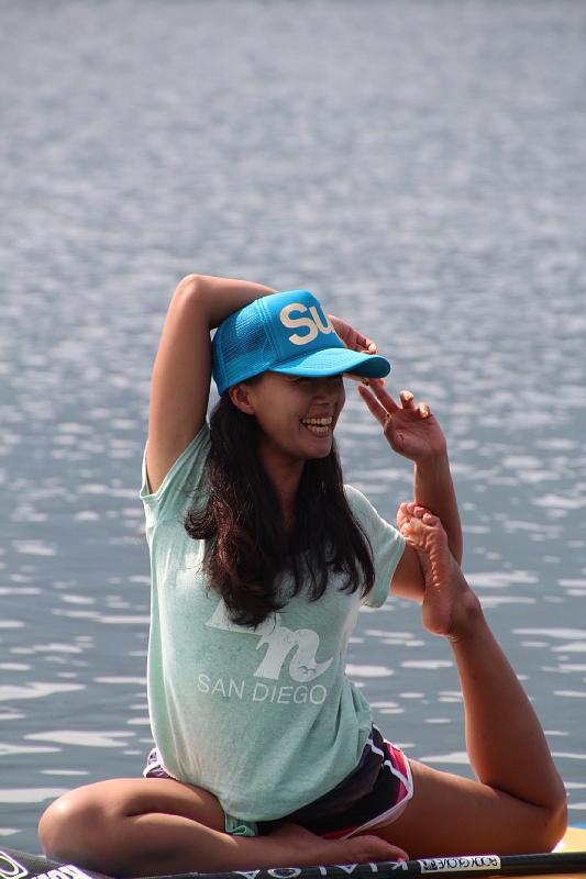 サーフボードの上でヨガをして笑顔の田中律子