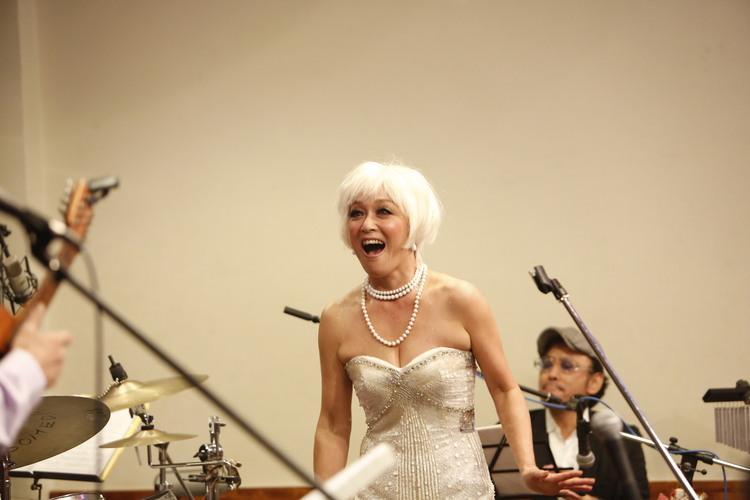 白髪のかつらに白いドレスを着て歌っているキムラ緑子の画像