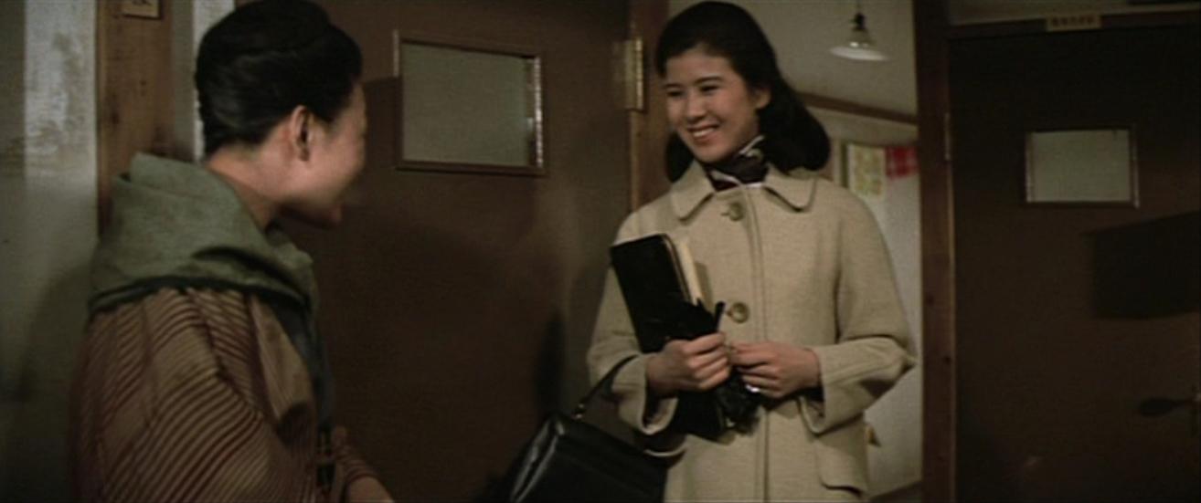 コート着て微笑み返す演技をするハーフアップした映画の中の十朱幸代